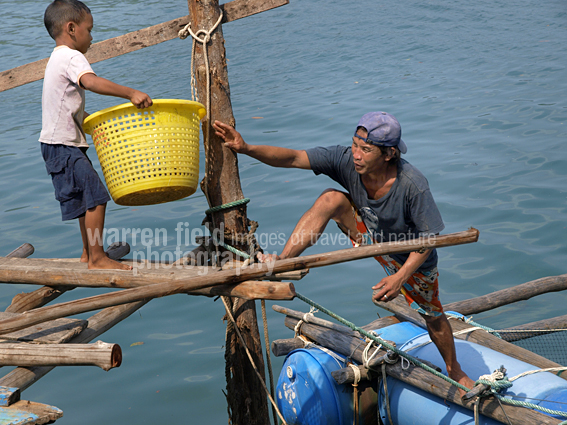 Son helping father at one of the harbour seafood restaurants at Koh Kood, Thailand