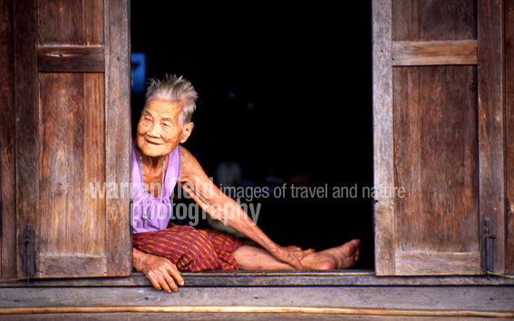 Elderly woman looks out on passing boat traffic, Thonburi canals, Bangkok.